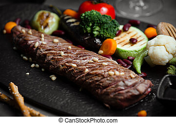 Lamb steak with roasted and grilled vegetables on black stone board