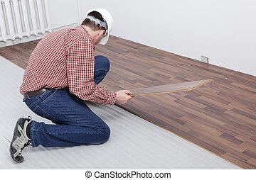 Laminate flooring installation - Man making the laminate...