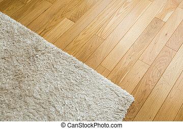 Laminate parquete floor. Light wooden texture. Beige soft carpet.