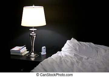 Lamp - A lit nightstand lamp in a bedroom