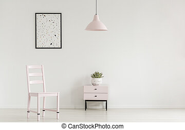 Lamp above cabinet with plant next to chair in white living room interior with poster. Real photo