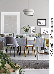 Lamp above chairs and table in grey dining room interior with mockup and posters. Real photo