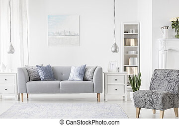 Lamp above white cabinet between plant and grey sofa in simple flat interior with armchair. Real photo