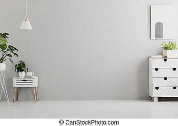 Lamp above white cabinet with plant in grey living room interior with poster and copy space. Real photo. Place for your sofa