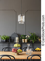 Lamp above wooden table with fruits in grey dining room interior with plants. Real photo
