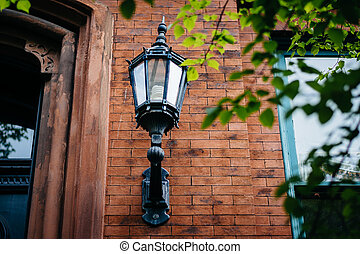 Lamp affixed to a house in Mount Vernon, Baltimore, Maryland.