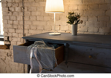 Lamp and bouquet with flowers on an old chest of drawers background brick wall