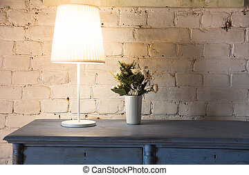 Lamp and bouquet with flowers on an old chest of drawers