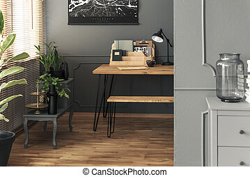 Lamp and organiser on wooden desk in grey home office interior with black poster. Real photo