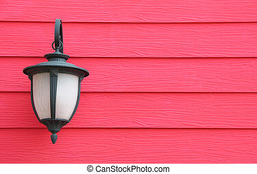 Lamp hanging on wooden wall