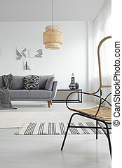 Lamp in white spacious apartment interior with patterned blanket on grey couch. Real photo