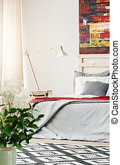 Lamp next to grey bed in bright bedroom interior with red painting and flowers. Real photo