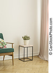 Lamp next to wooden cabinet with plant in white living room interior with poster. Real photo