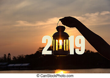 lamp on hand in sunbeam over sunset with 2019 . power and idea concept