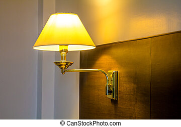 Lamp on headboard in bedroom