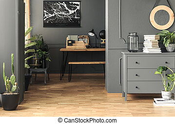 Lamp on wooden desk in grey study room interior with poster, plant and cabinet. Real photo