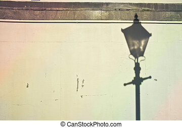 Lamp post shadow cast on a stone wall