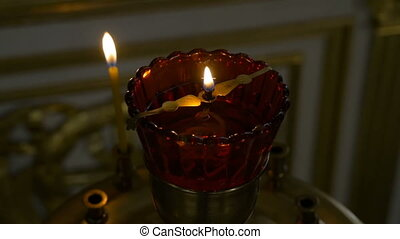 Burning candles in front of the altar in the church. Praying...