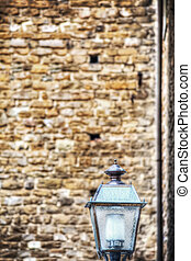 lamppost with a brick wall in the background