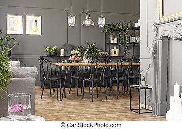 Lamps above table and black chairs in grey dining room interior with posters and plants. Real photo