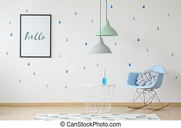 Lamps above table in kids room interior with blue rocking chair and poster on the wallpaper. Real photo