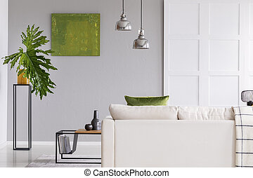 Lamps above white sofa in simple living room interior with green painting and plant on table. Real photo