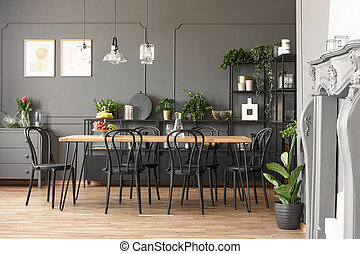 Lamps above wooden table and black chairs in grey dining room interior with plants. Real photo