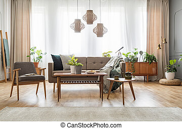 Lamps above wooden table with flowers in bright living room interior with sofa and armchair. Real photo