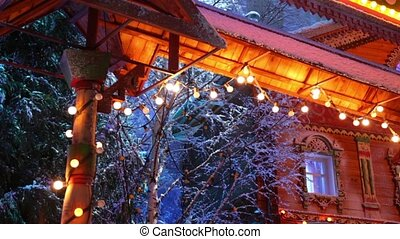 Lamps flashes on garland stretched along trees and carved...