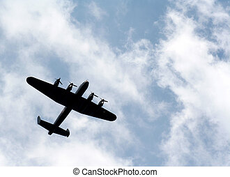 The silhouette of a Lancaster bomber against blue sky with white puffy clouds.