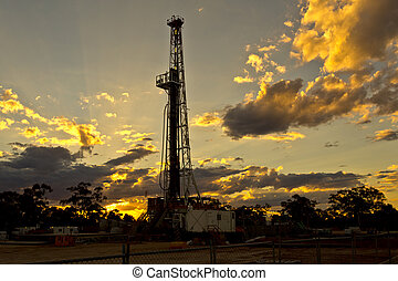 Land Drilling Rig at Sunset - Land rig drilling during a...