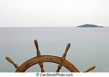 Old ship's steering wheel on great ocean background with a small island ahead.