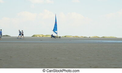 Land sailing - A pilot in a sail wagon rolls through the deserted sandy beach