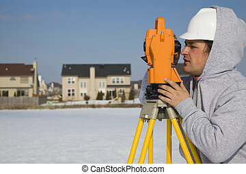 Land surveying during the winter - suburban area.