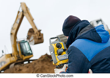 surveyor worker with geodesy equipment device theodolite at land surveying outdoors