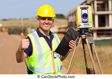 land surveyor giving thumb up - senior surveyor giving thumb...