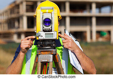 land surveyor looking through theodolite