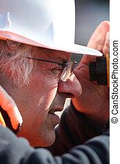 Land surveyor peering into an altometer