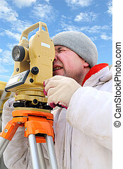 Land surveyor working with theodolite equipment at a construction site in winter over blue sky