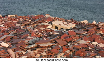 Landfill by the lake. - Bricks and building materials from...