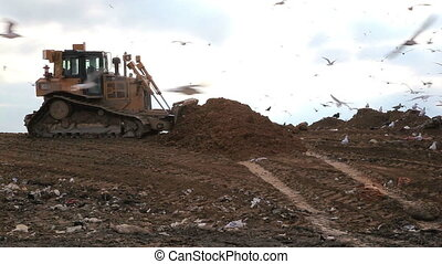 Landfill covering ground - Truck in a landfill covering...