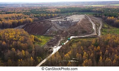 Landfill. A huge pile of garbage surrounded by forest. Garbage trucks carry garbage to a landfill, top view.
