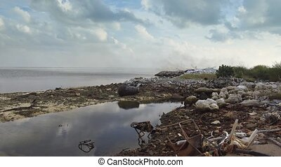 Dark smoke issues from a garbage pile as waste is burned at the landfill on Maafushi Island, in the Maldives. UltraHD stock footage