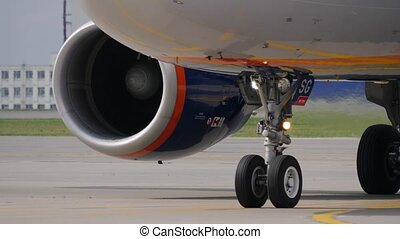 Landing gear and engine of jet airliner. Fuselage reflects taxiway marking