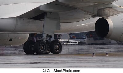 Landing gear and engine of jetliner taxiing on wet airport ramp. Sunlight spots on fuselage