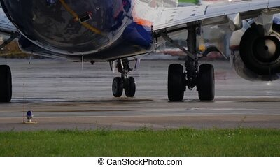 Landing gear of Boeing 777. Aircraft turns on taxiway. Jet engine makes heat haze