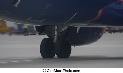 Landing gear of jet airliner taxiing at airport. Engine works and makes heat haze