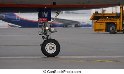 Landing gear of taxiing aircraft. Fore wheel of airplane moving on airport apron