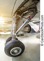 Landing gear under the wing of the aircraft in a hangar at the maintenance service.