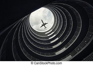 Landing passenger airplane, seen from inside of a car parking